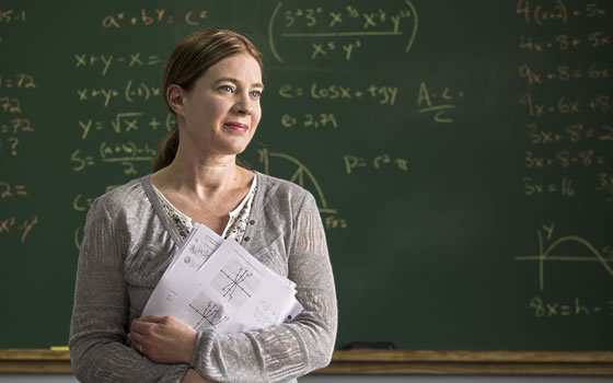 A proud math teacher stands in front of chalkboard