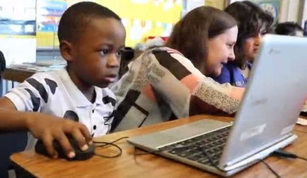A boy learning on a personal computer in a classroom.