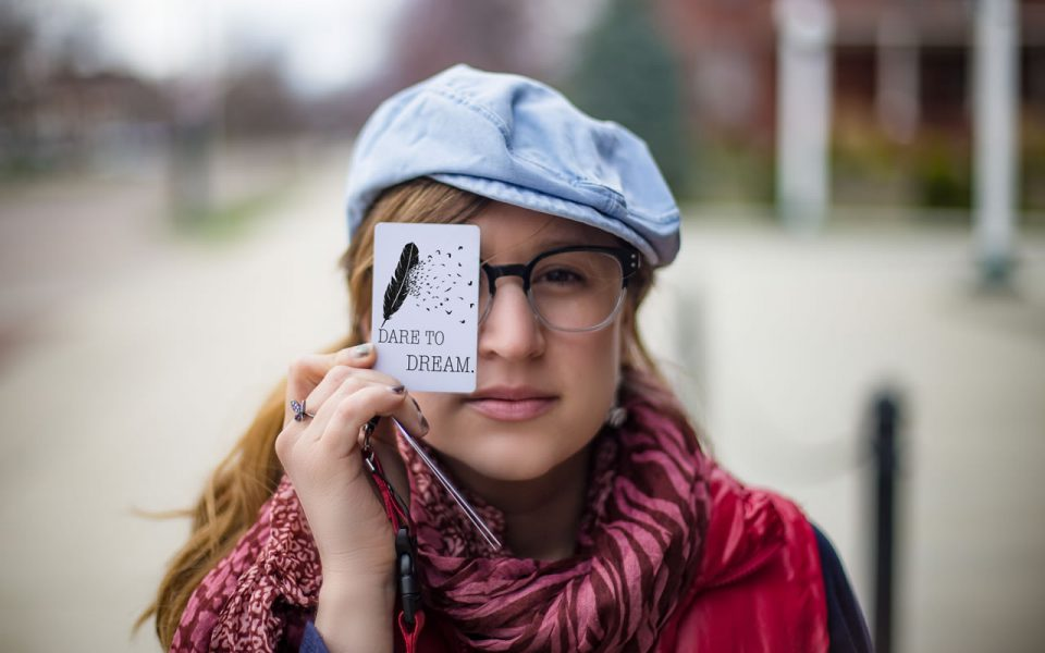 "A student holding a card that says ""dare to dream."""