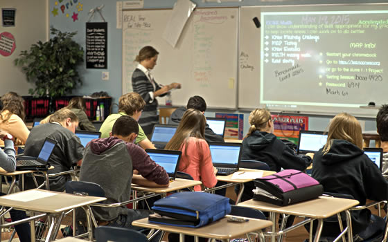 High school teacher intructs classroom students with laptops.
